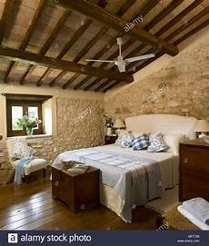 da letto con parete in pietra a country bedroom with exposed rustic walls and