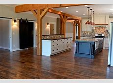 Open concept kitchen with cedar posts, white distressed cabinets, custom bar and island