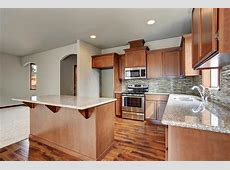 Kitchen Room Interior With Brown Cabinets, Kitchen Island, Granite Counter Tops. Stock Photo