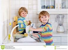 boys helping in kitchen with washing dishes