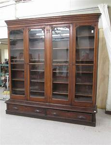 a large four door walnut cabinet bookcas