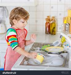 clothes for boys dishes blond kid boy washing dishes stock photo 274190687