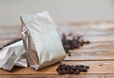 Coffee Bag Metallic Coffee Bag With Coffee Beans Behind Free Photo