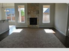 Living room and slate tile fireplace with carpet insert and wood surround. Builder: www