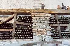 scaffali per bottiglie di dentro una cantina con le bottiglie invecchiate della