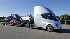 here is a tesla semi truck carrying a tesla car carrier