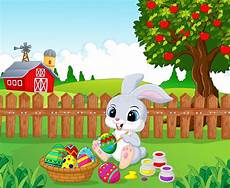 easter bunny painting an egg in the garden
