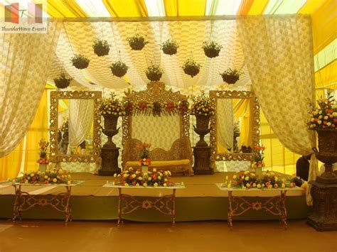 A simple stage decor with yellow drapes, gold seats, and