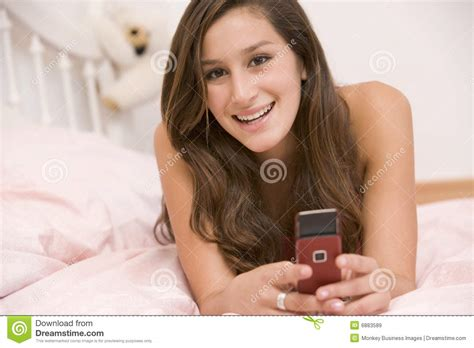 Smiling Girl Using Mobile Phone In Bed Royalty Free Stock | teenage girl lying on her bed using mobile phone royalty