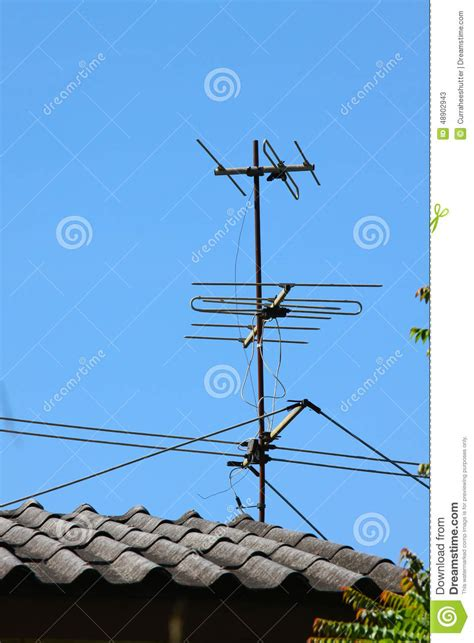Tv Roof tv antenna on house roof with blue sky stock image