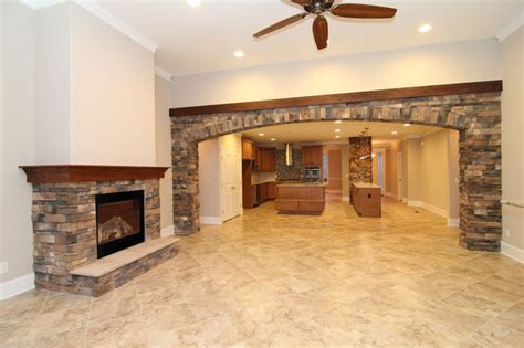 archways and raised ceilings features to put your great room with stone fireplace and archway transitional