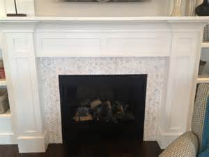 white stained wooden fireplace mantel above white glass