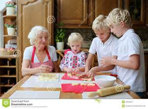 Home Interior And Gifts grandmother with grandkids cooking in the kitchen stock