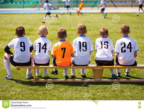football team bench young football players young soccer team sitting on wooden