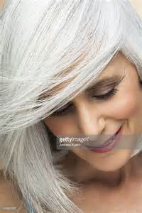 looking with grey hair woman with silvery grey hair looking down stock photo