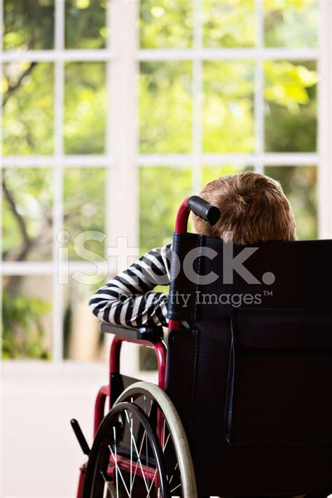 film kijken the woman in the window backview van jongen in rolstoel verlangend kijken via