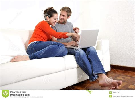 couch sitting happy couple working or online shopping on their laptop on