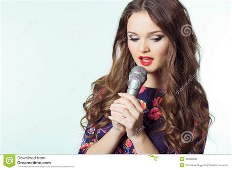 portrait of a beautiful elegant girl singer brunette with long hair with a microphone