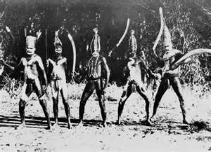 Aboriginal people in ceremonial dress pose for a photograph of a