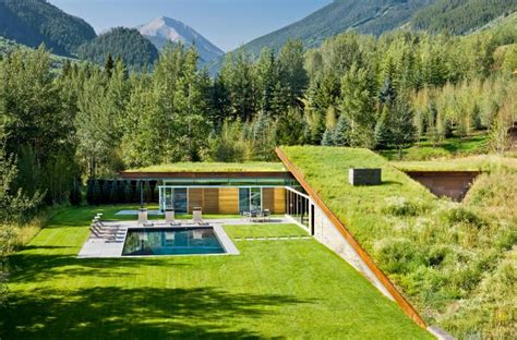 homes in the mountains modern house with roof that integrated into the mountains