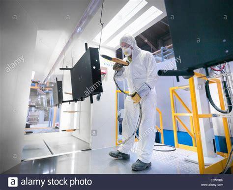 Selang Untuk Spray Gun worker powder coating parts in paint spray booth in sheet metal stock photo royalty free