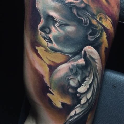 stonework style colored biceps tattoo of small baby angel