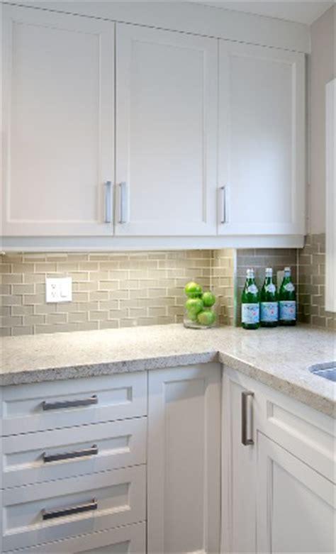 neutral glass tile backsplash white shaker cabinets smoke gray glass subway tile