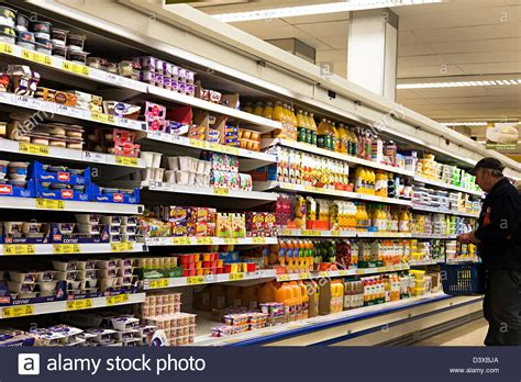 Shelf Of Orange Juice by Shopping In Tesco In Front Of Cooled Shelves Of Orange