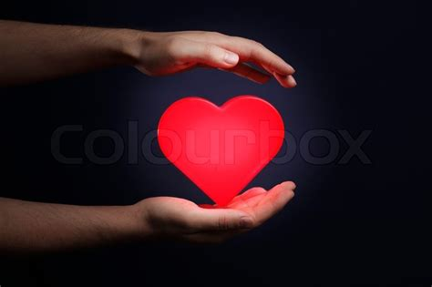 heart shape man scaping man holding a red glowing heart in his hands stock photo