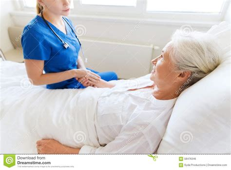 bed medicine doctor or nurse visiting senior woman at hospital stock