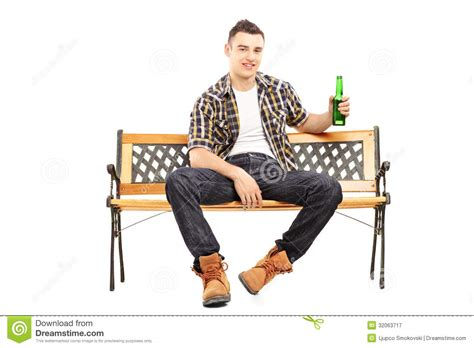 man sitting on bench young smiling man sitting on a bench and holding a beer bottle male models picture