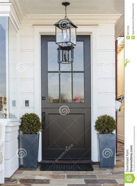 black front door framed  plants stock photo image