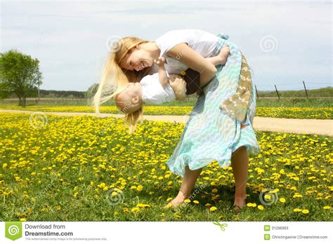 mom swings baby around mother playing with baby in dandelion field stock photos