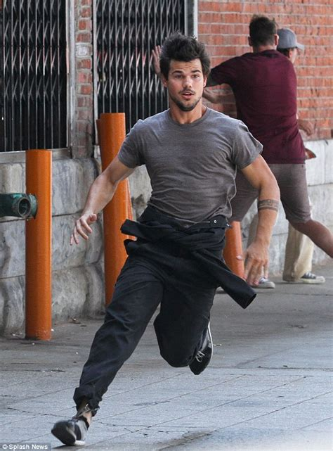 taylor lautner jumps off a ledge and leaps over cars as he
