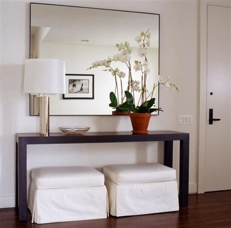 white entry table slipcovered white ottomans and modern wood console table with chrome l and large wall mirror