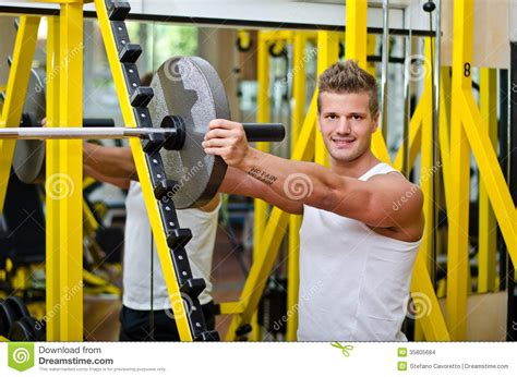 putting weight on a smiling in putting weight disc on barbell stock images image 35805684