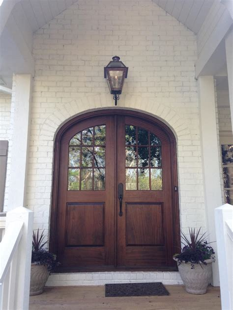 Brown Arched Glass Front Door On White Brick Home Build Arched Front Doors