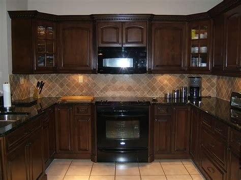 do you tile under kitchen cabinets brown kitchen cabinets with dark countertop and lighter