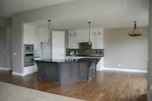 Kitchen with grey island white cabinets zerra green slate backsplash