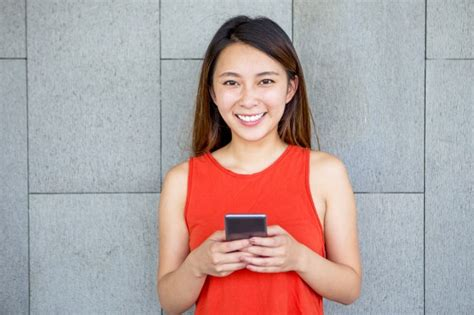 who is the asian girl in the mobile strike commercial portrait of smiling asian girl with mobile phone photo