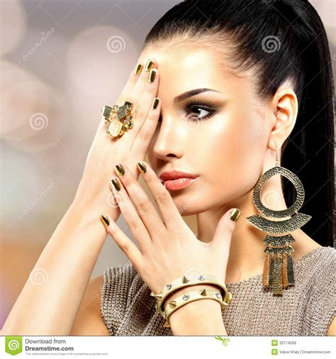 beautiful fashion model in jewelery and lila manicure beautiful fashion woman with black makeup and golden
