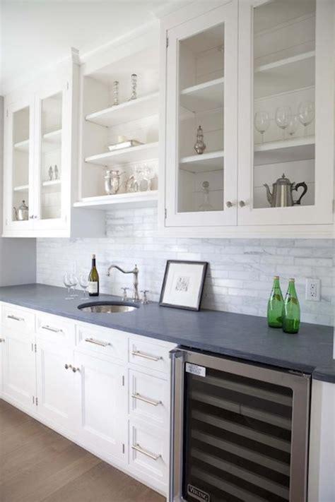 pale aqua pantry door white shaker cabinets black corner island prep sink next to glass front wine fridge