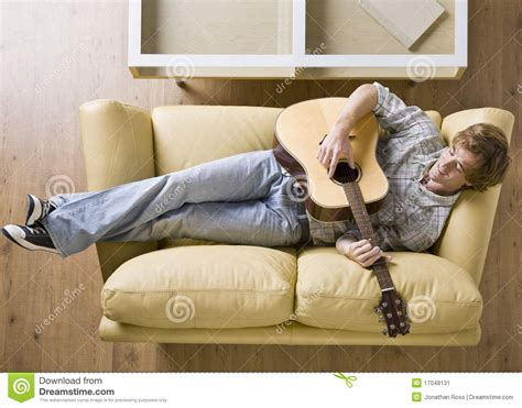 laying couch man laying on sofa playing guitar stock image image