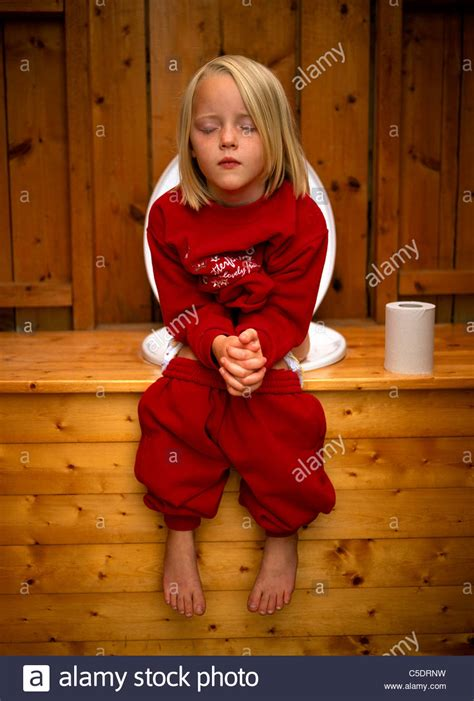 a girl using the bathroom little girl using the toilet with tissue roll on wooden