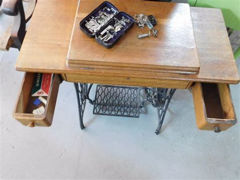 singer treadle sewing machine in wooden cabinet with two