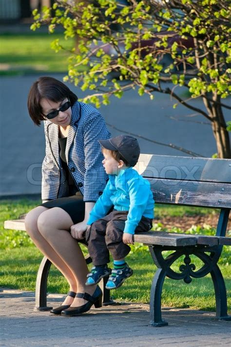 rape bench happy mother and son sitting on bench in city park stock