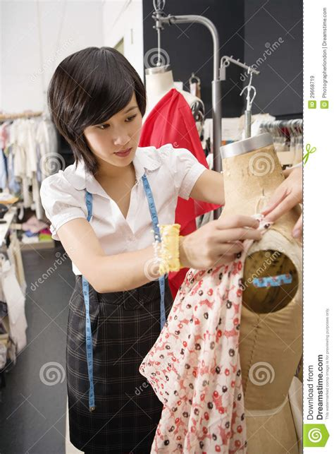 themes taken by fashion designers female fashion designer pinning costume on mannequin stock