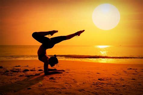 imagenes yoga en el mar mujer haciendo el pino en la playa al atardecer
