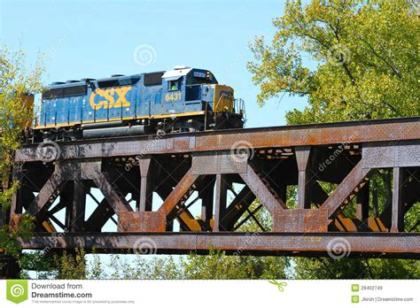 freight train crossing a steel railroad truss river bridge