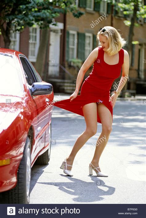 being caught and dressed as a girl as punishment youtube woman in red dress caught by a red car s door stock photo